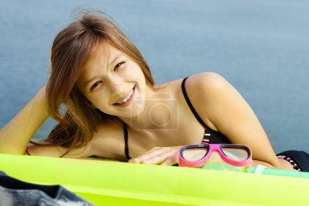 Beautiful girl in bikini lying on mattress
