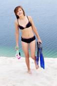 Girl in bikini carrying scubadiving equipment