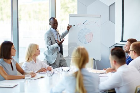 Photo pour Homme d'affaires africain pointant du doigt le graphique du développement financier - image libre de droit