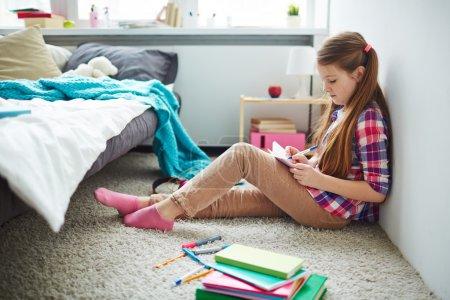Teenage Girl writing in notebook