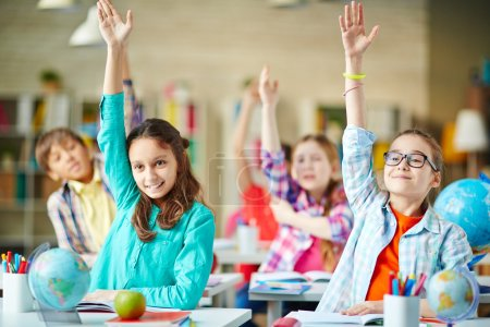 Photo for Intelligent group of school children raising their hands in to answer a question - Royalty Free Image
