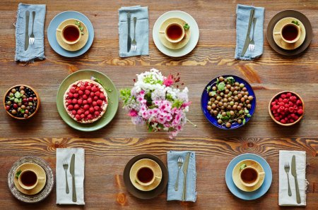 Photo for Fresh berries, tea and cake on served table - Royalty Free Image