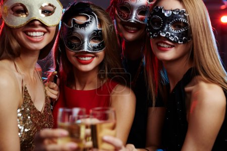 Young girls in masquerade masks
