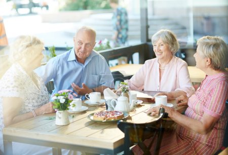 Photo for Seniors talking in cafe on sunny day - Royalty Free Image