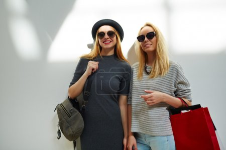 Photo for Stylish girls looking at camera with smiles - Royalty Free Image