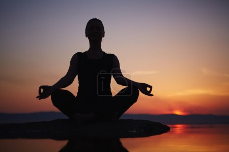 Photo for Woman meditating near lake - Royalty Free Image