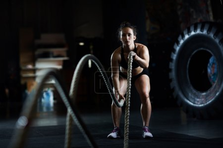 Photo for Sporty woman practicing exercise with battle ropes - Royalty Free Image