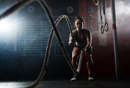 Photo for Fit woman swewating during training with ropes - Royalty Free Image