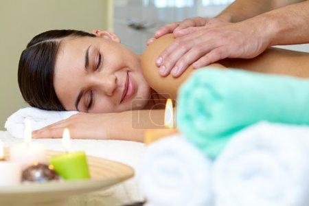 Photo pour Portrait de jeune femme se trouvant dans le salon spa et profiter de la procédure de massage - image libre de droit