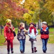 Portrait of happy schoolkids talking while going t...