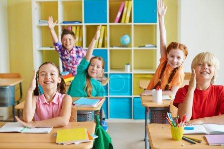 Happy classmates raising hands