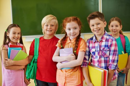 Photo for Five friendly classmates looking at camera on background of blackboard - Royalty Free Image