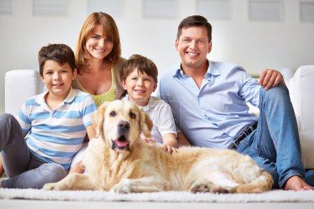 Photo pour Famille heureuse avec deux garçons et un chien souriant à la caméra - image libre de droit