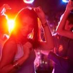 Pretty girls dancing in night club on background o...