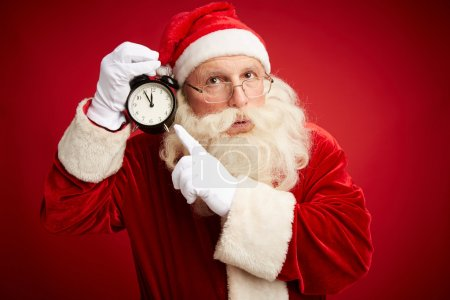 Photo for Pensive Santa Claus pointing at clock showing five minutes to midnight - Royalty Free Image