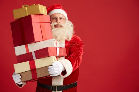 Photo for Happy Santa Claus with xmas presents looking at camera - Royalty Free Image