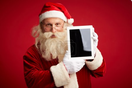 Photo for Portrait of Santa Claus with touchscreen looking at camera - Royalty Free Image