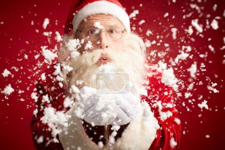 Photo for Santa Claus blowing snow and looking at camera - Royalty Free Image