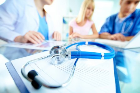 Photo for Stethoscope and document on background of doctors and patient working with laptop - Royalty Free Image