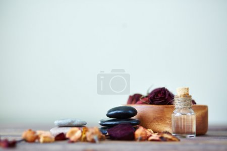 Photo for Dry roses in bowl, spa stones and aromatic essence in bottle - Royalty Free Image