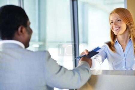 Photo pour Jolie jeune femme donnant passeport et billet de retour à l'homme d'affaires au comptoir d'enregistrement de l'aéroport - image libre de droit