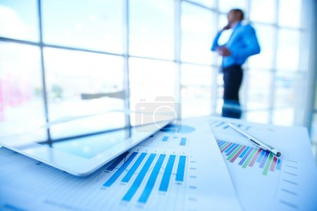 Photo for Business documents, touchpad and pen on background of businessman by office window - Royalty Free Image
