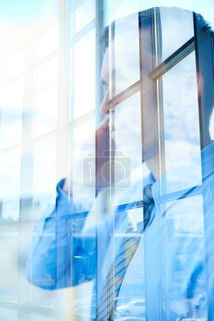 Foto de Joven hombre de negocios llamando en ventana de oficina - Imagen libre de derechos