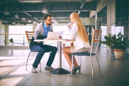 Photo pour Deux hommes d'affaires regardant dans les journaux à la réunion - image libre de droit