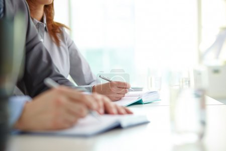 Foto de Hand of businesswoman with ballpoint over open notebook at convention - Imagen libre de derechos