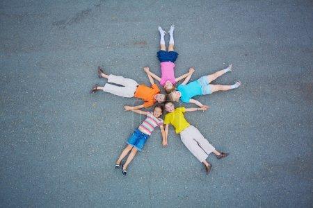 Photo pour Petits amis couchés sur de l'asphalte tête contre tête et regardant la caméra - image libre de droit