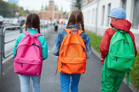Photo pour Sacs d'écoliers avec des sacs à dos colorés se déplaçant dans la rue - image libre de droit
