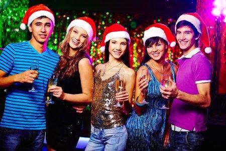 Photo pour Jeunes amis glamour dans les casquettes du Père Noël regardant la caméra tout en grillant avec du champagne - image libre de droit