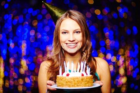 Photo pour Fille souriante avec gâteau d'anniversaire en regardant la caméra sur fond scintillant - image libre de droit
