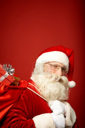 Photo for Portrait of Santa Claus carrying sack with gifts and looking at camera - Royalty Free Image
