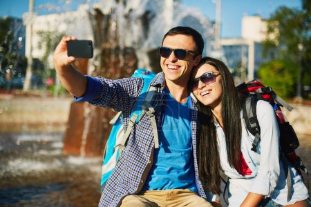 Photo for Traveling young couple taking selfy on cellphone outdoors - Royalty Free Image