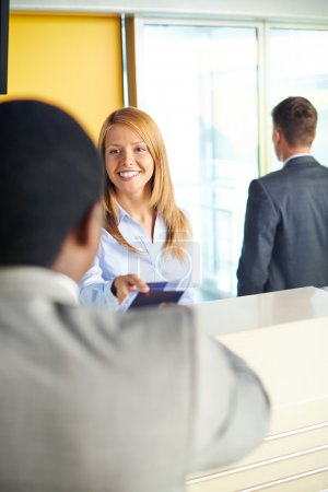 Woman returning documents to businessman