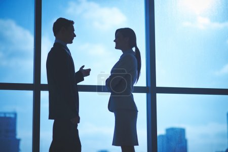 Business partners talking by the window
