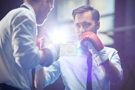 Photo for Serious businessman in boxing gloves looking at his rival before attack - Royalty Free Image