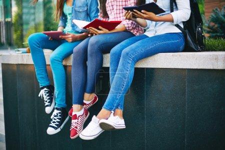 Photo pour Casual adolescent filles en jeans lecture à l'extérieur - image libre de droit