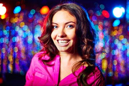Photo pour Charmante femme souriante regardant la caméra sur fond scintillant - image libre de droit