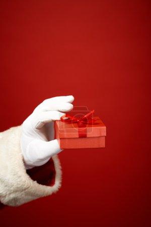 Santa hand holding gift box