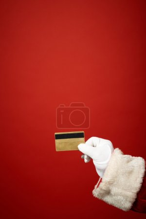 Photo for Santa Claus gloved hand holding plastic card on red background - Royalty Free Image