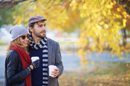 Couple drinking coffee in autumn park