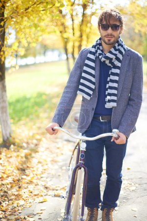 Man with bicycle in autumn park
