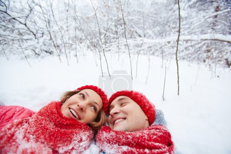 Man and woman lying in snow