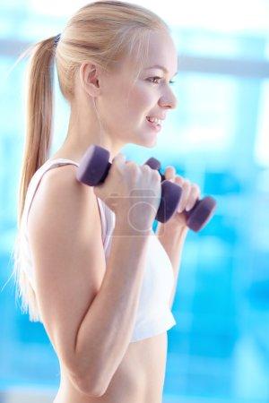 Girl lifting dumbbells in gym