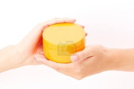 Photo pour Gros plan des mains tenant boîte jaune avec crème protectrice ou baume isolé sur fond blanc - image libre de droit