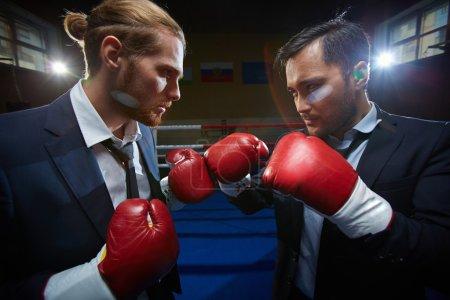 Photo pour Deux hommes d'affaires en vetu et gants de boxe sur ring de boxe - image libre de droit