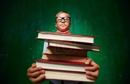 Photo for Cute elementary pupil holding heavy stack of textbooks - Royalty Free Image