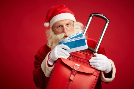 Photo for Santa Claus with red leather suitcase and airline tickets on red background - Royalty Free Image